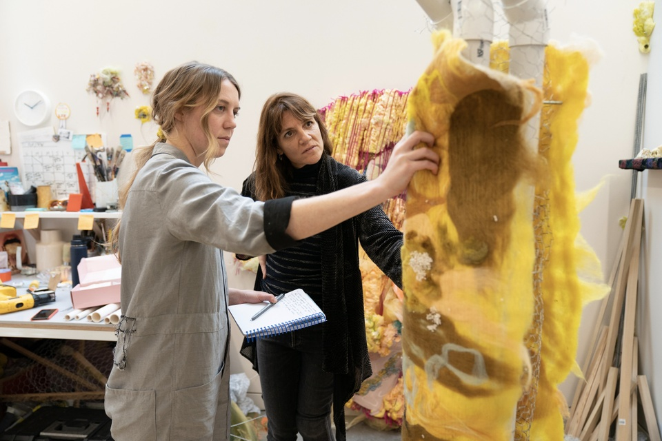 A student shows a bright yellow artwork to Dana Levy in studio.