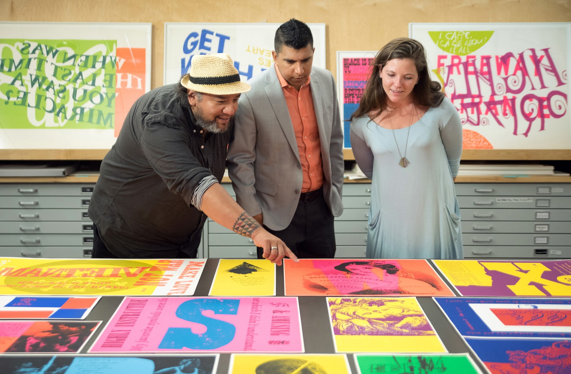 Three people look down at a table covered in colorful screenprints. One of them, a tanned, middle-aged, Native man points to the prints.