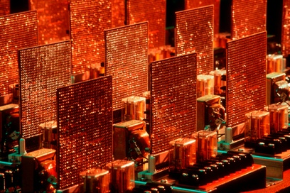 Taken by the photojournalist Erich Hartmann in 1982, this vibrant, color photograph features a close-up of an IBM circuit board for a computer. Taken at a slight angle, Hartmann shows three rows of three power amplifiers, with the fourth row cropped and pictured nearly out of frame. They appear as if they are rectangular-shaped skyscrapers, with lights dazzling across thousands of windows. The power amplifiers in the foreground are crisp and in focus, and as the image recedes, they become slightly blurred. The overall hue of the photograph is a burnt orange color, with a few turquoise highlights streaked across the body of specific hardware parts caused from the camera's flash.