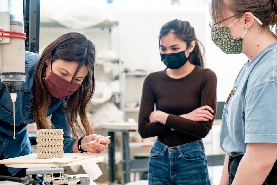 Three people wearing face coverings gather around a machine being used to make a 3D printed ceramics piece, which has a circular shape.