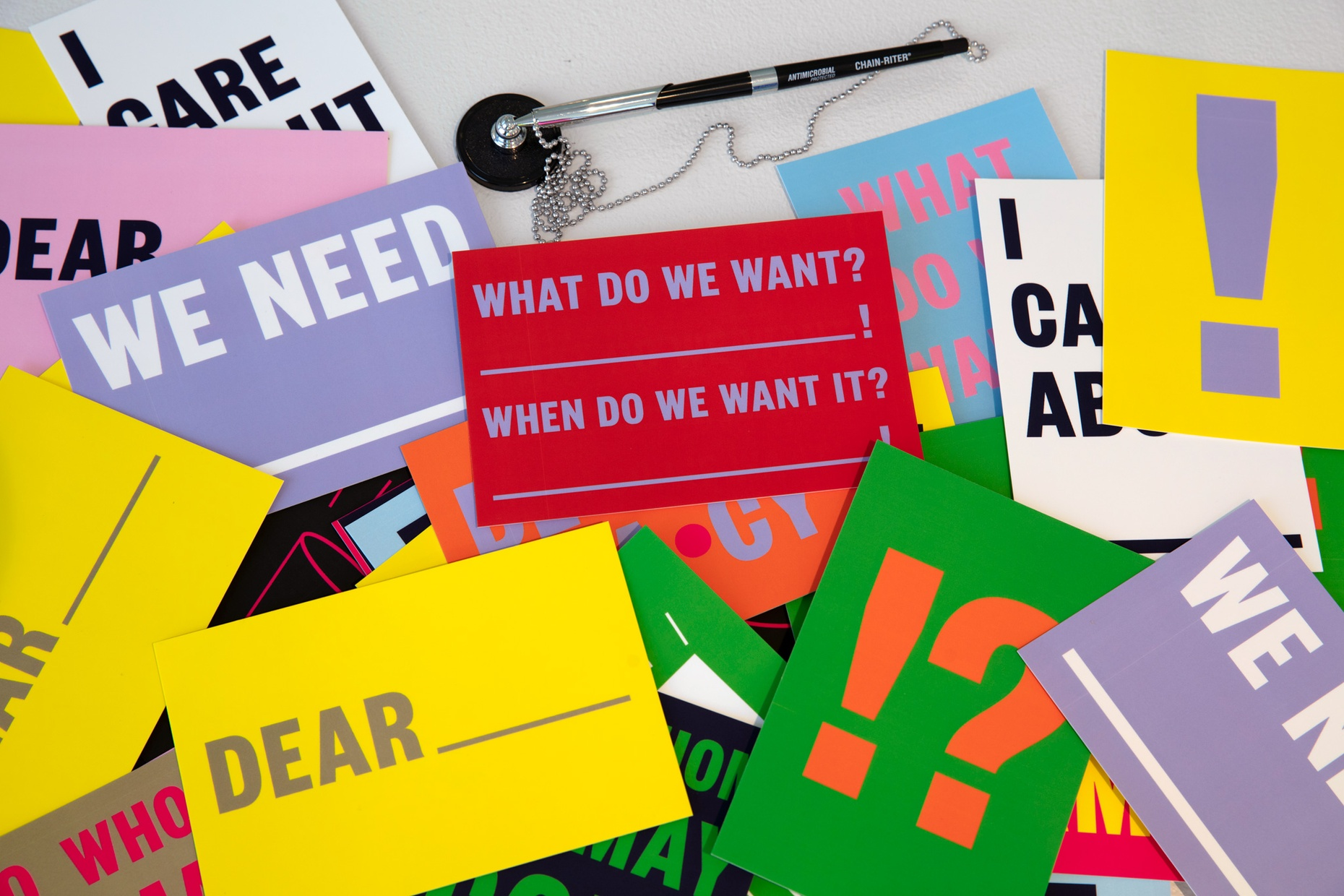 """Various colorful postcards with text like """"Dear___"""", """"We Need ____"""", and """"What do we want? _____! When do we want it? ______!"""" spread out on a table."""