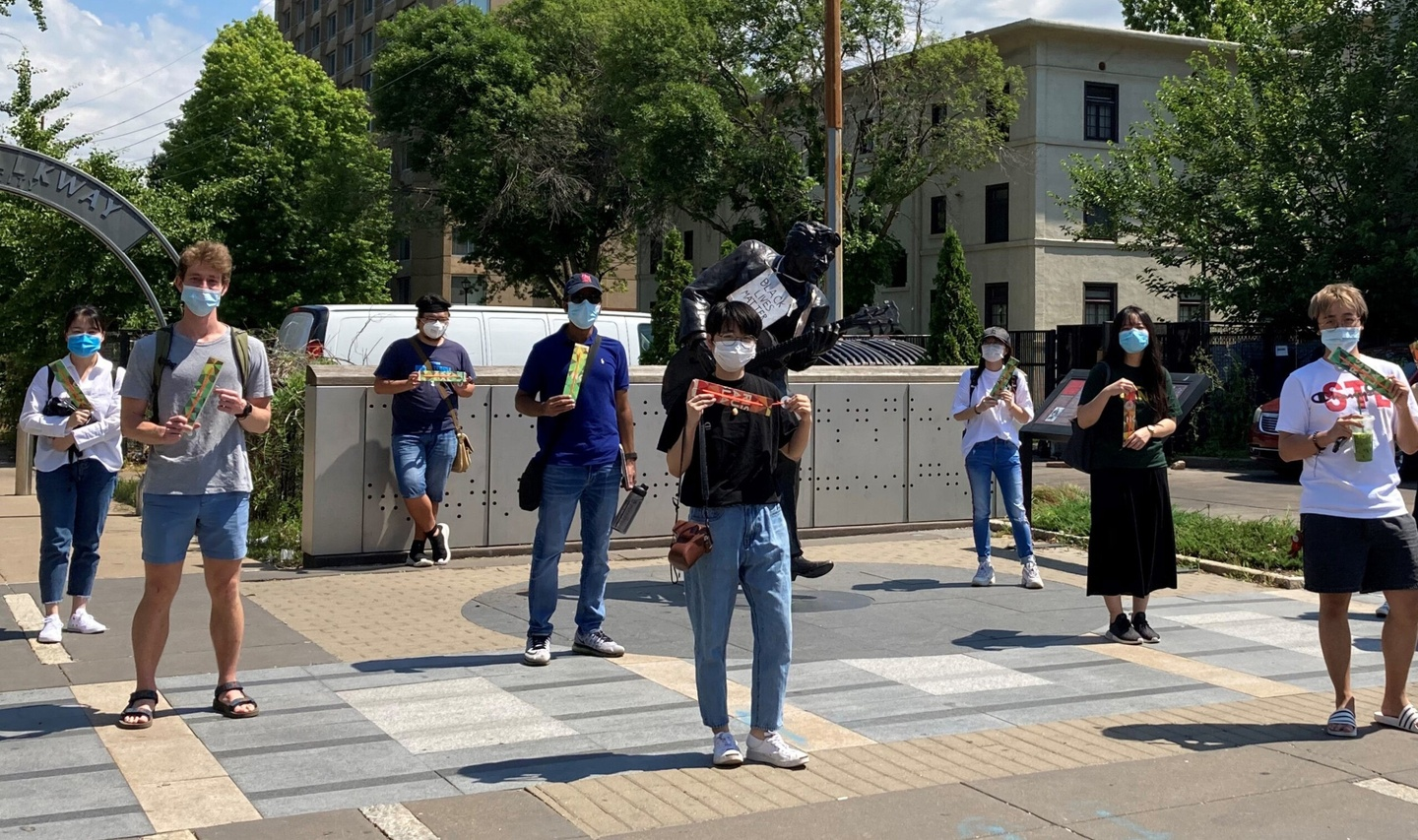 Eight students stand in three rows, spaced at least 6 feet apart from each other and wearing protective face masks; they are also holding rulers to measure social distance. They are standing outside in University City, Missouri.