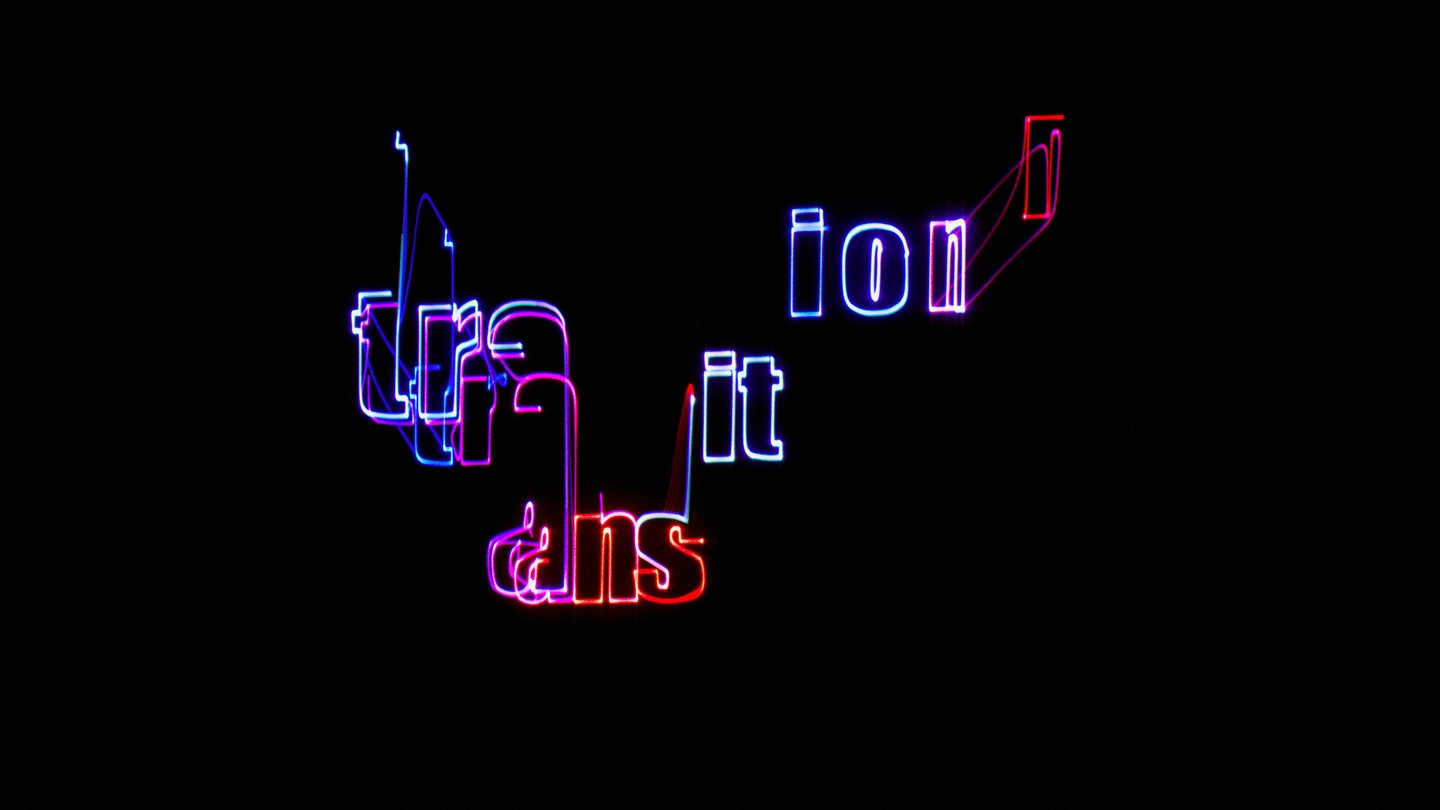 The outlines of letters in neon are set against a black background. The letters are split in groups and set in a U-shaped pattern, spelling the word Transition.