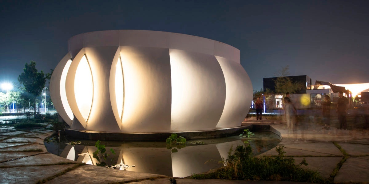 Photo of the exterior facade of a single-story home lit up at night. The exterior is composed of curved, overlapping panels, arrayed around a central axis like a blossoming flower.