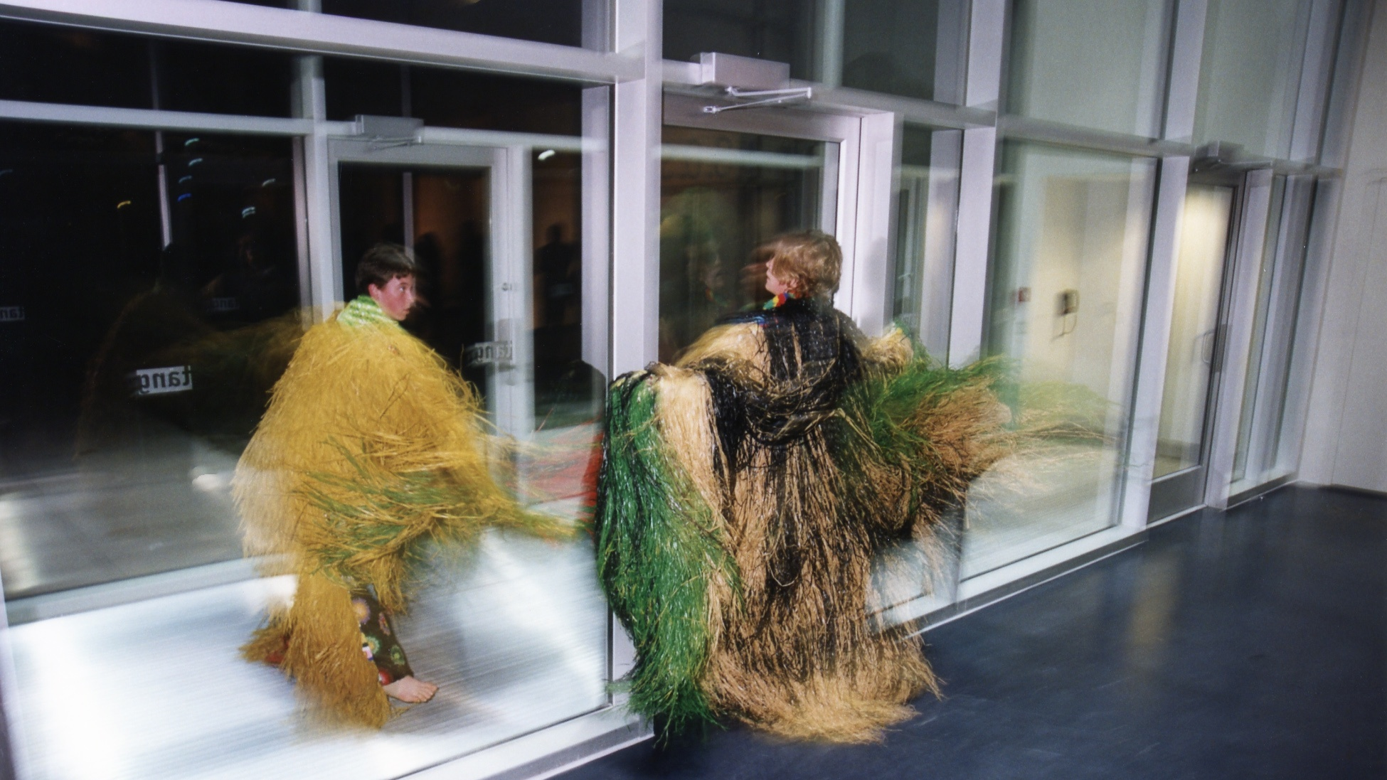 Two light-skinned people twirl in robes made of long grasses next to a glass entryway.