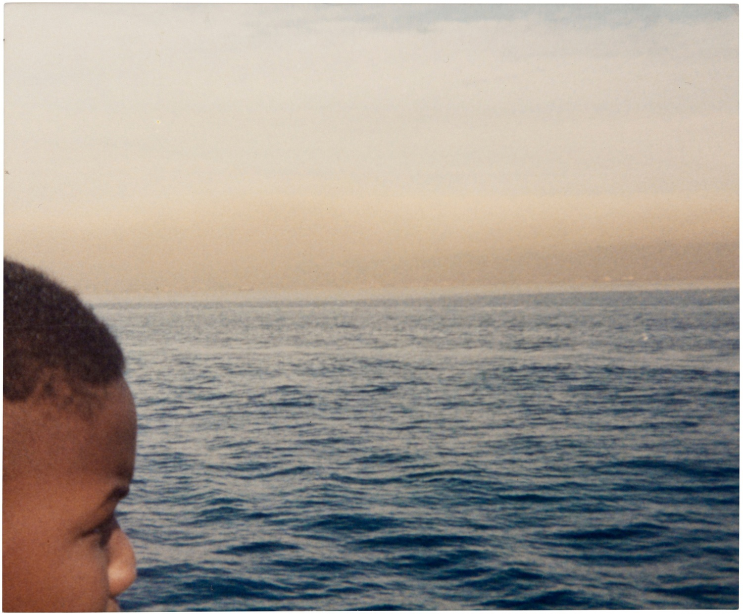 A photograph by an unknown artist of a vast body of water and a young dark-skinned boy, partially in view, looking out over the landscape form the left side of the photo.