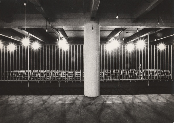 A black and white, landscape-oriented image from 1972 documenting Kate Millett's installation called *Terminal Piece*. A barrier of wooden-slatted bars spans the length of an otherwise vacuous, cement industrial space. Illuminated from above, and set behind these bars, are two long rows of wooden folding chairs facing out towards the viewer. A mannequin of a lone, Caucasian, female-presenting figure is seated in one chair in the back row (located at the viewer's right). The rest remain empty.