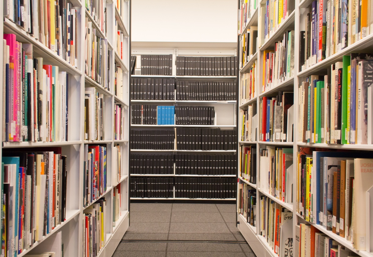 View down an aisle of books with bound periodicals on the bisecting wall.