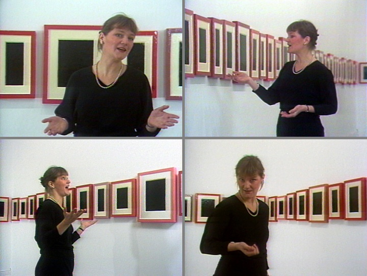 Four-panel image of video stills, showing an individual discussing a wall of repeating works, all square with red frames, white borders and black square interiors.