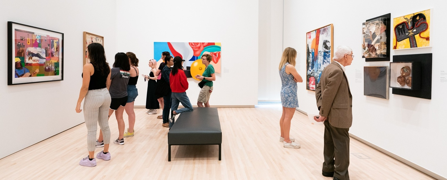 A dozen people mill around in the wing of a gallery showcasing brightly colored modern art.