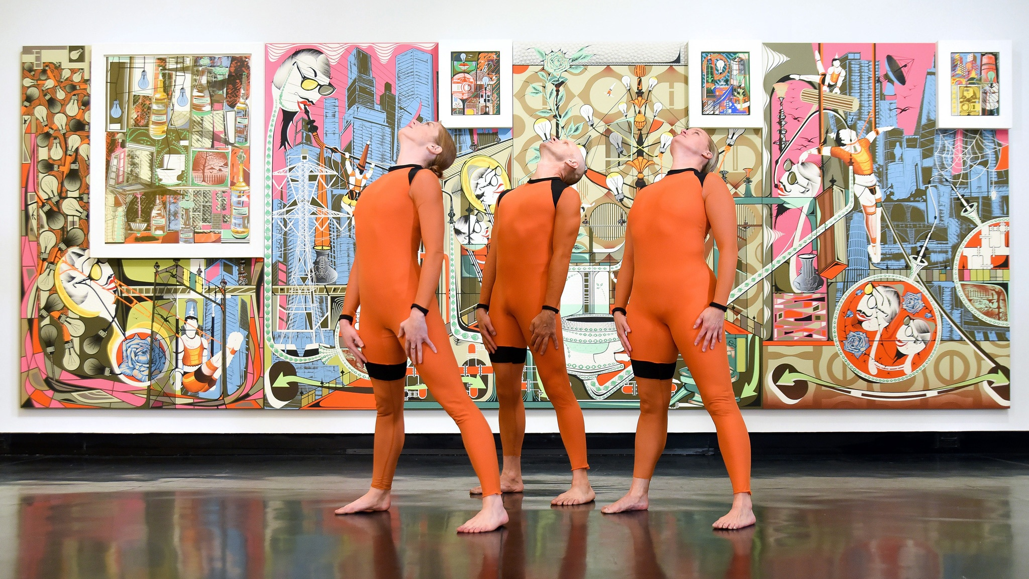 Three dancers in orange jumpsuits stand with their heads back in front of a large, abstract, colorful painting.