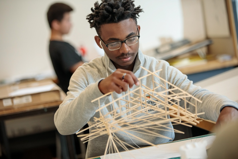 A person works on an elaborate architectural model of wooden sticks.