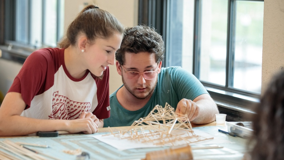 Two people inspect an architectural model built of wooden sticks.