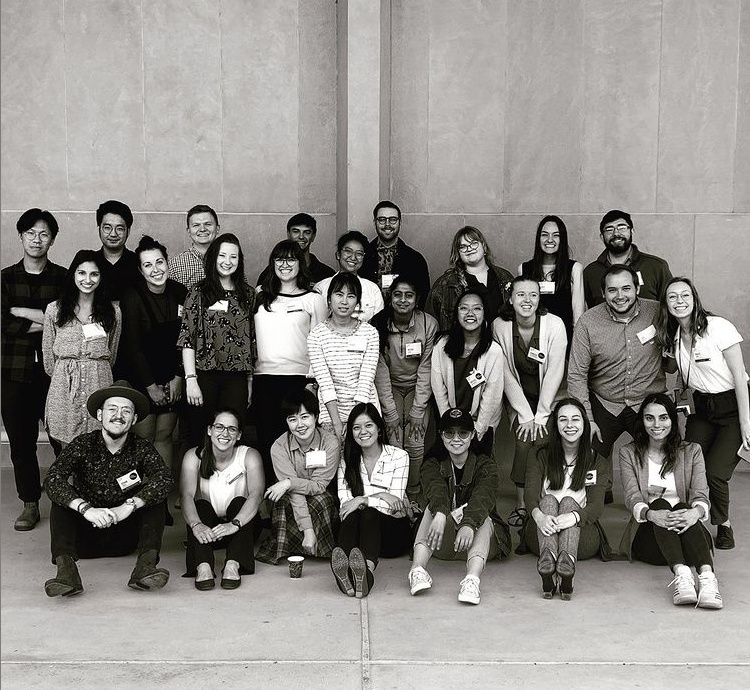 Black and white photo of many students in three rows posing for the camera against a concrete wall.