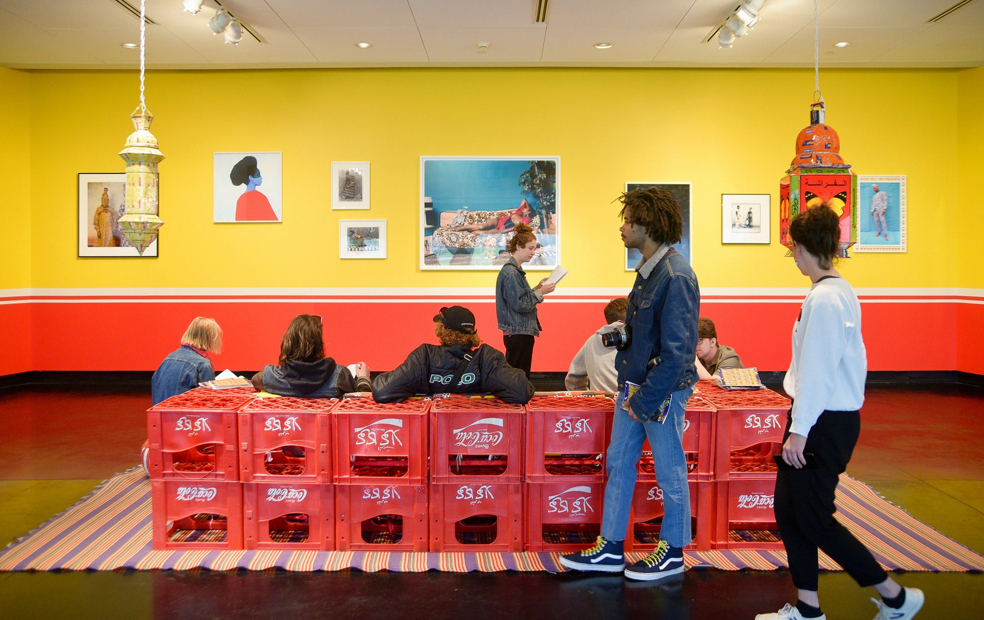 Two people walk past a group of people sitting in a couch made of Coca Cola crates looking at a yellow wall with artwork hung on it.