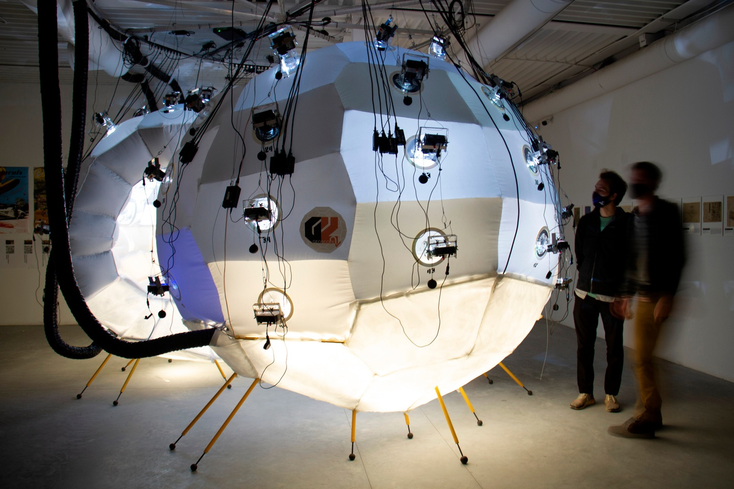 A split-sphere, multimedia installation in a darkened room, with two people looking at it. The sculptures are two large, seemingly inflatable paneled spheres, tied down with cords and lit from underneath, with rounded portholes for light and cameras.