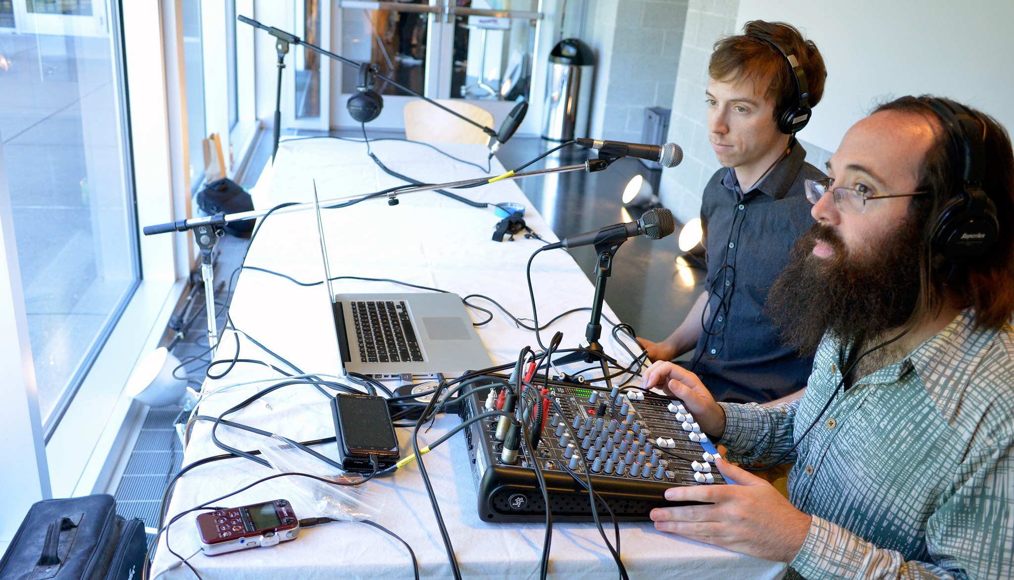 Two white men, one older and one younger, sit at a white table with mic stands and a sound board facing a wall of windows.