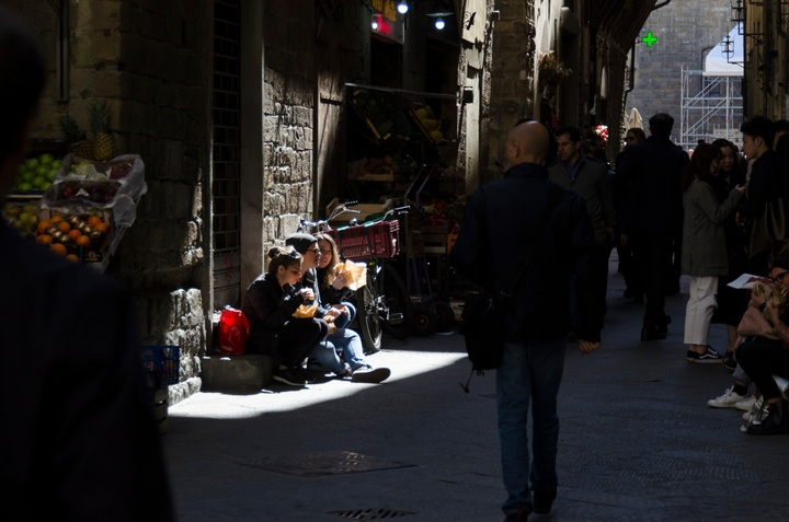 Three friends eating sandwiches on a stoop in the sunlight. The rest of the narrow street is in shadow.