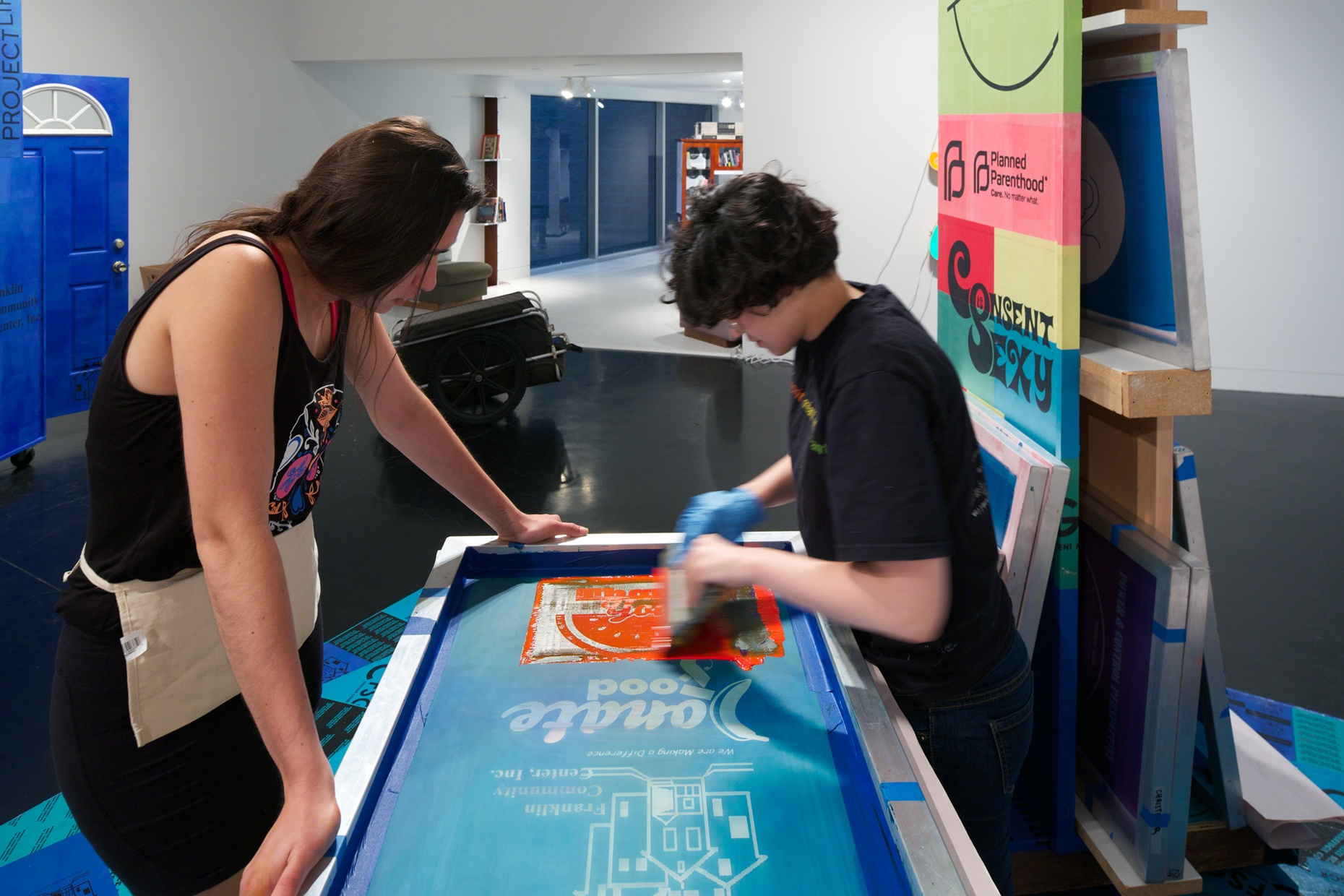 Two light-skinned, young people work on a screenprint in a gallery space.