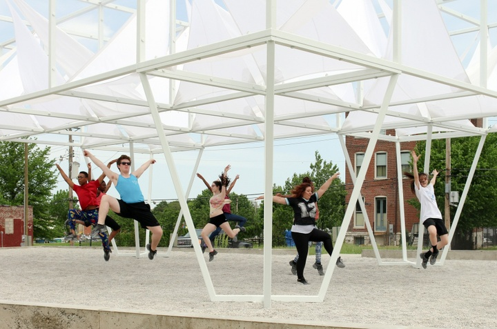 A group of people dance under a pavilion with white sails.