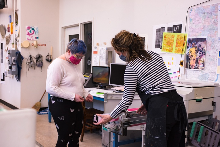 A person with short blue hair watches while a person in a black apron changes out a pink ink drum in the risograph machine. Colorful prints and safety goggles are hung on the wall behind them.