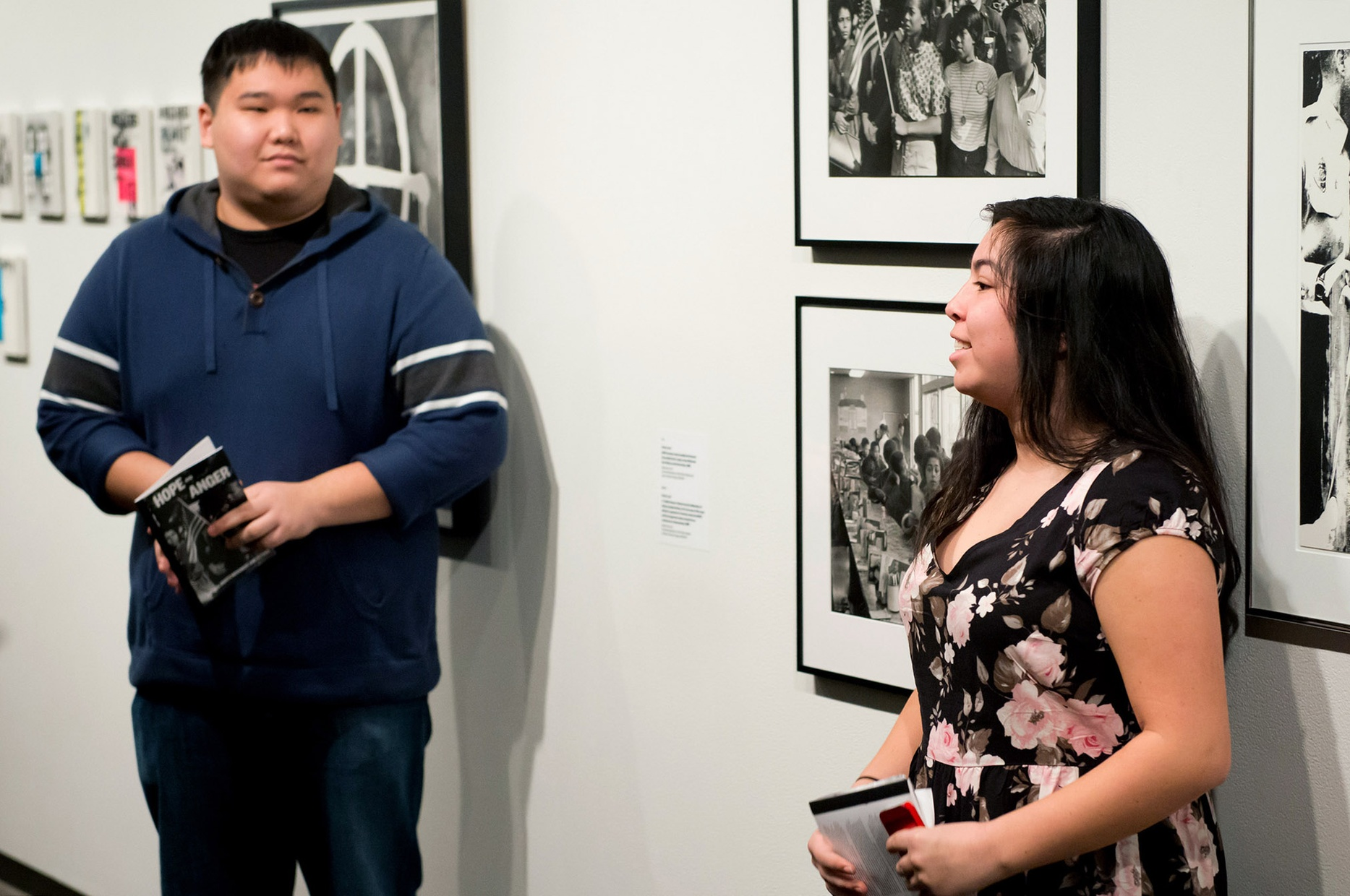 Two light-skinned, young people, one male and one female, stand in front of a wall with black and white photographs.