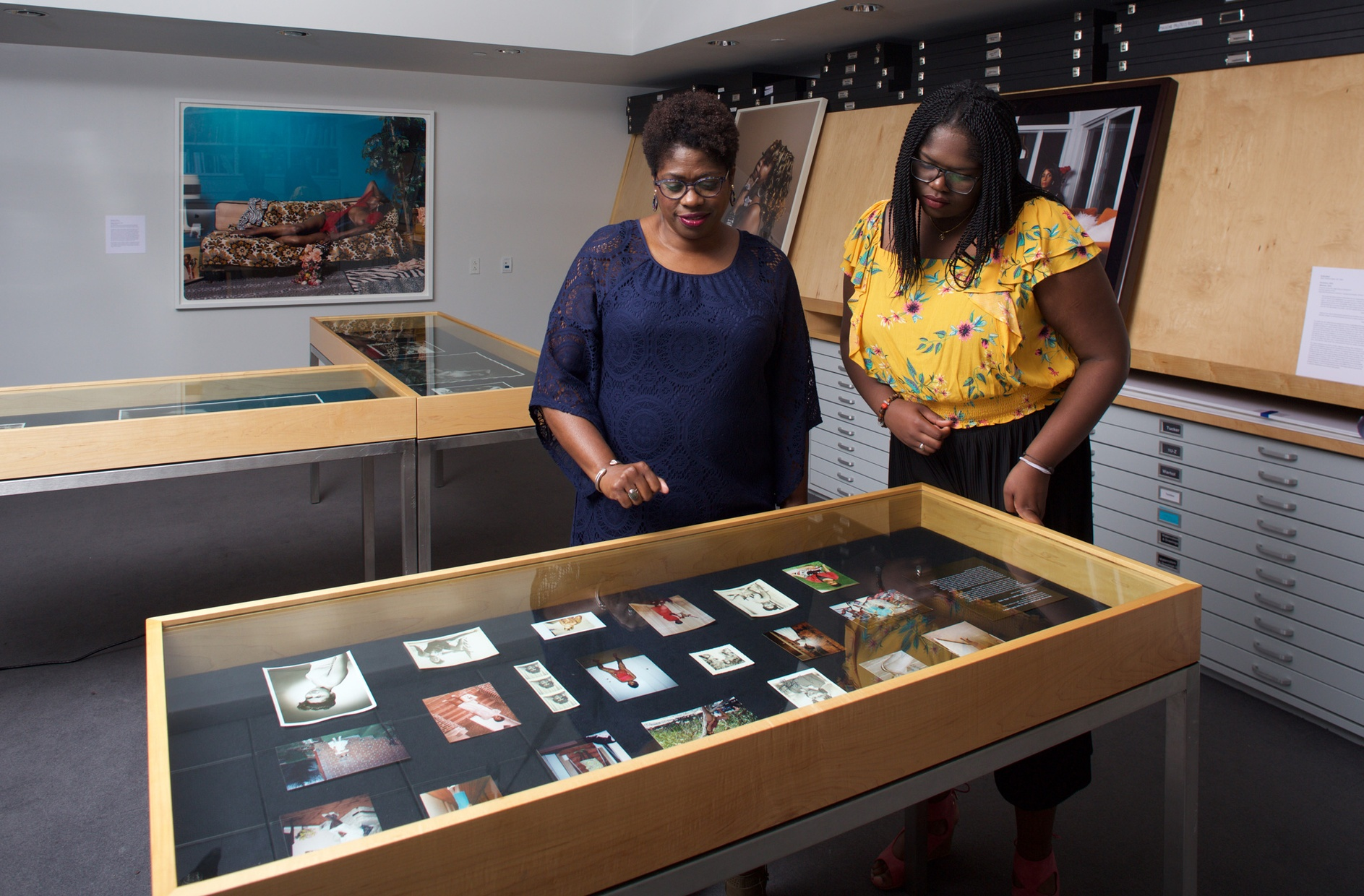 Two Black women, one older and one younger, look down at a glass case with photographs in it.
