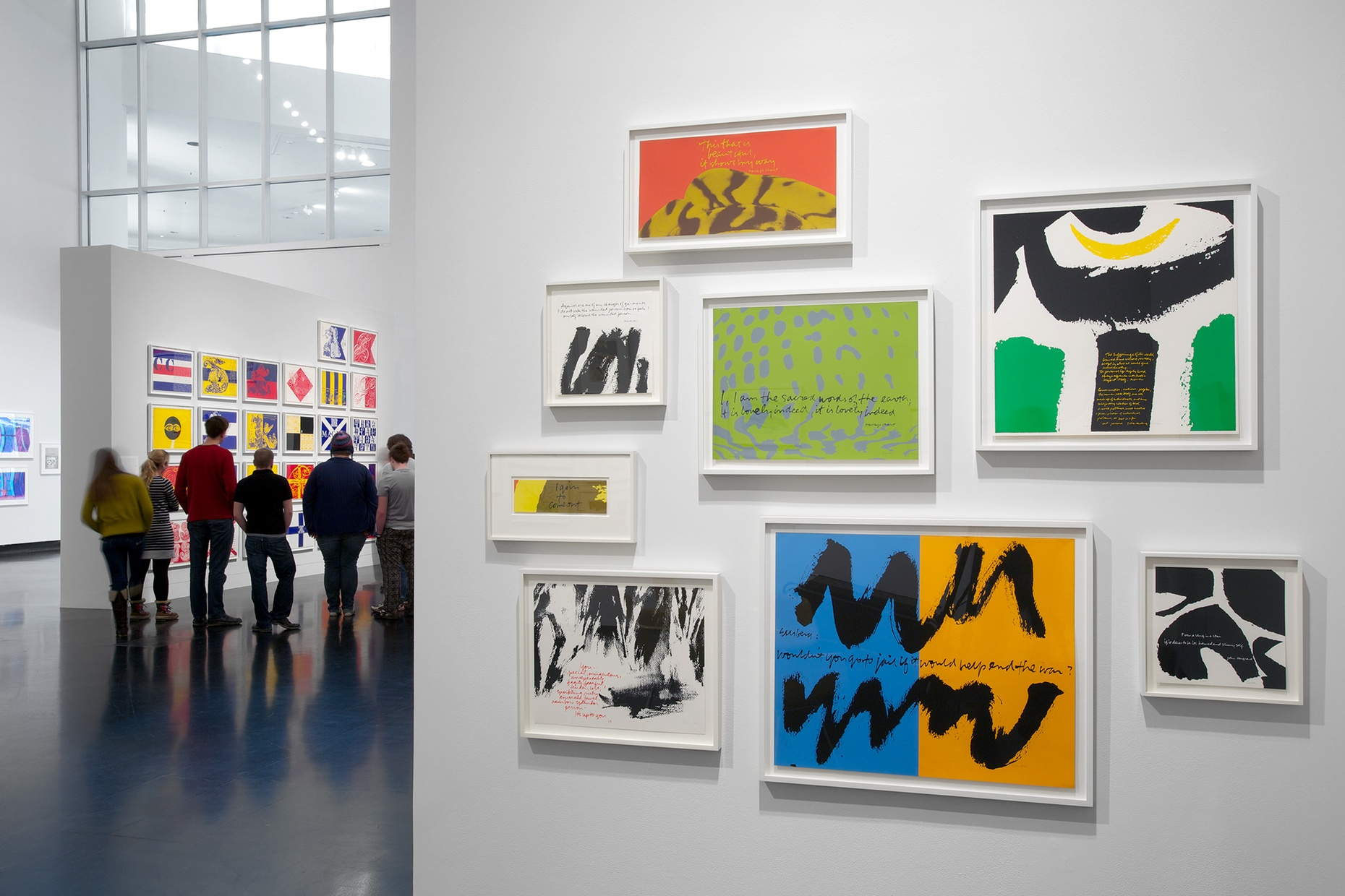 Eight colorful screen prints hung on a white wall with a group of people visible in the background.