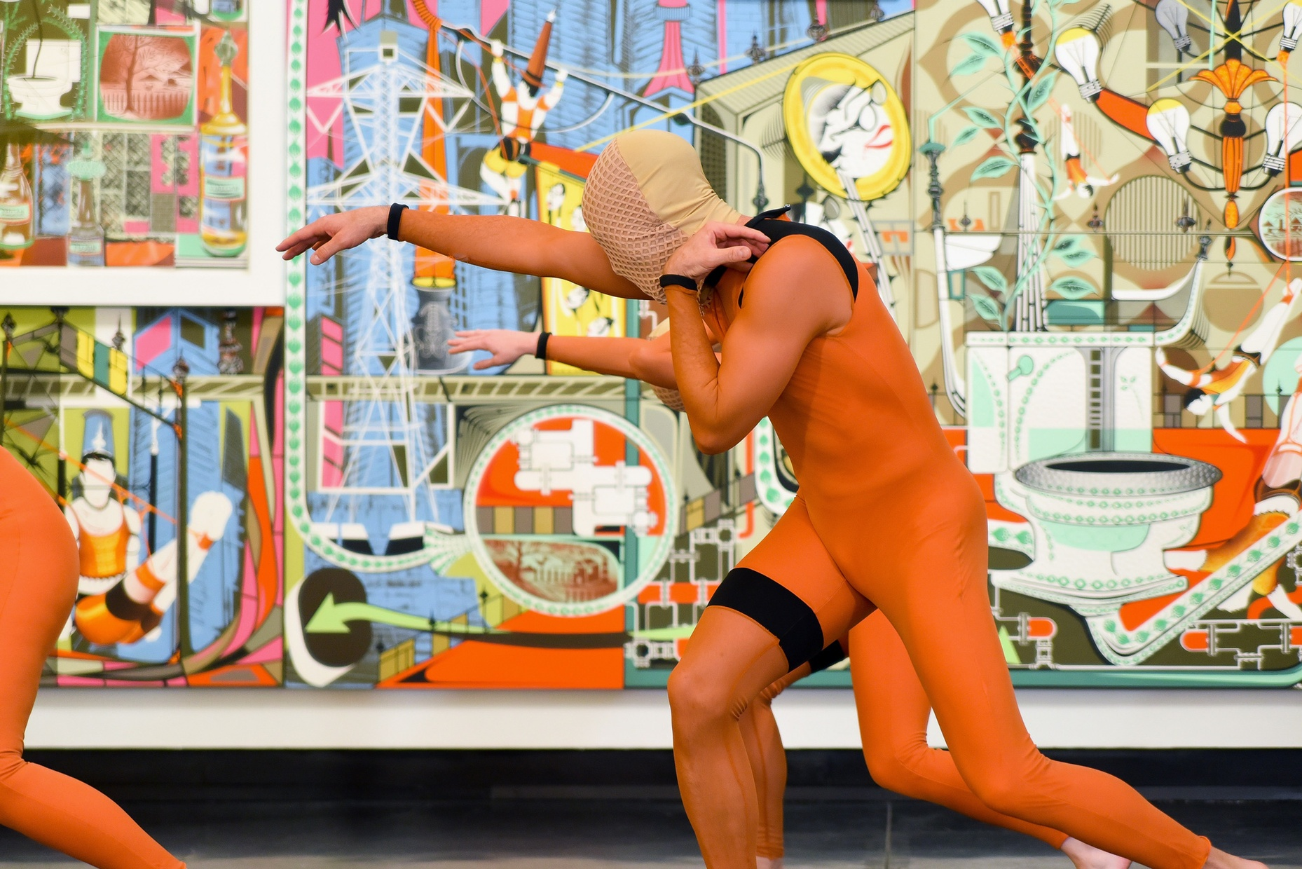 A figure in an orange jumpsuit with a covered face poses in front of a colorful painting.