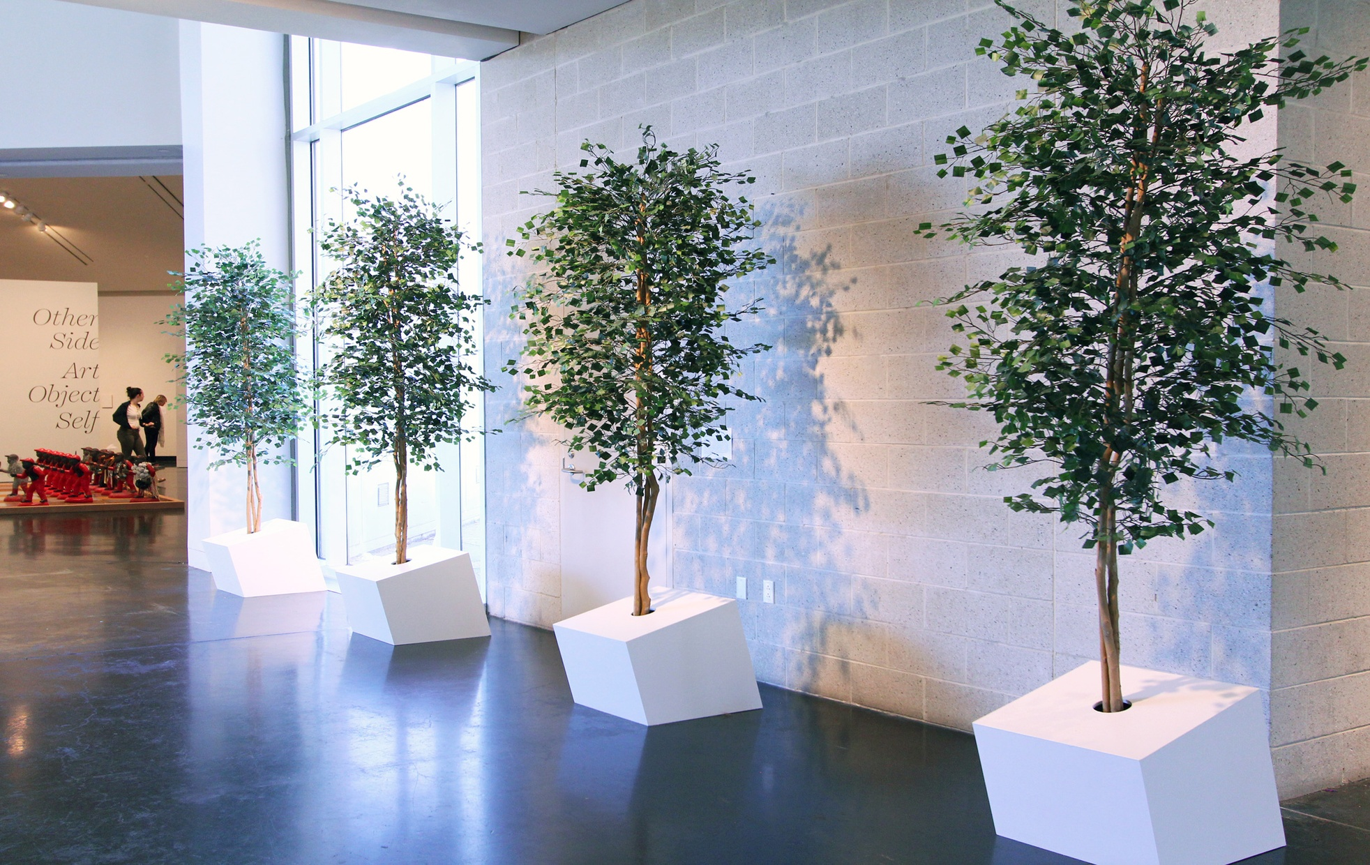 Four trees lined in a row sculpted with wood and paper green squares.