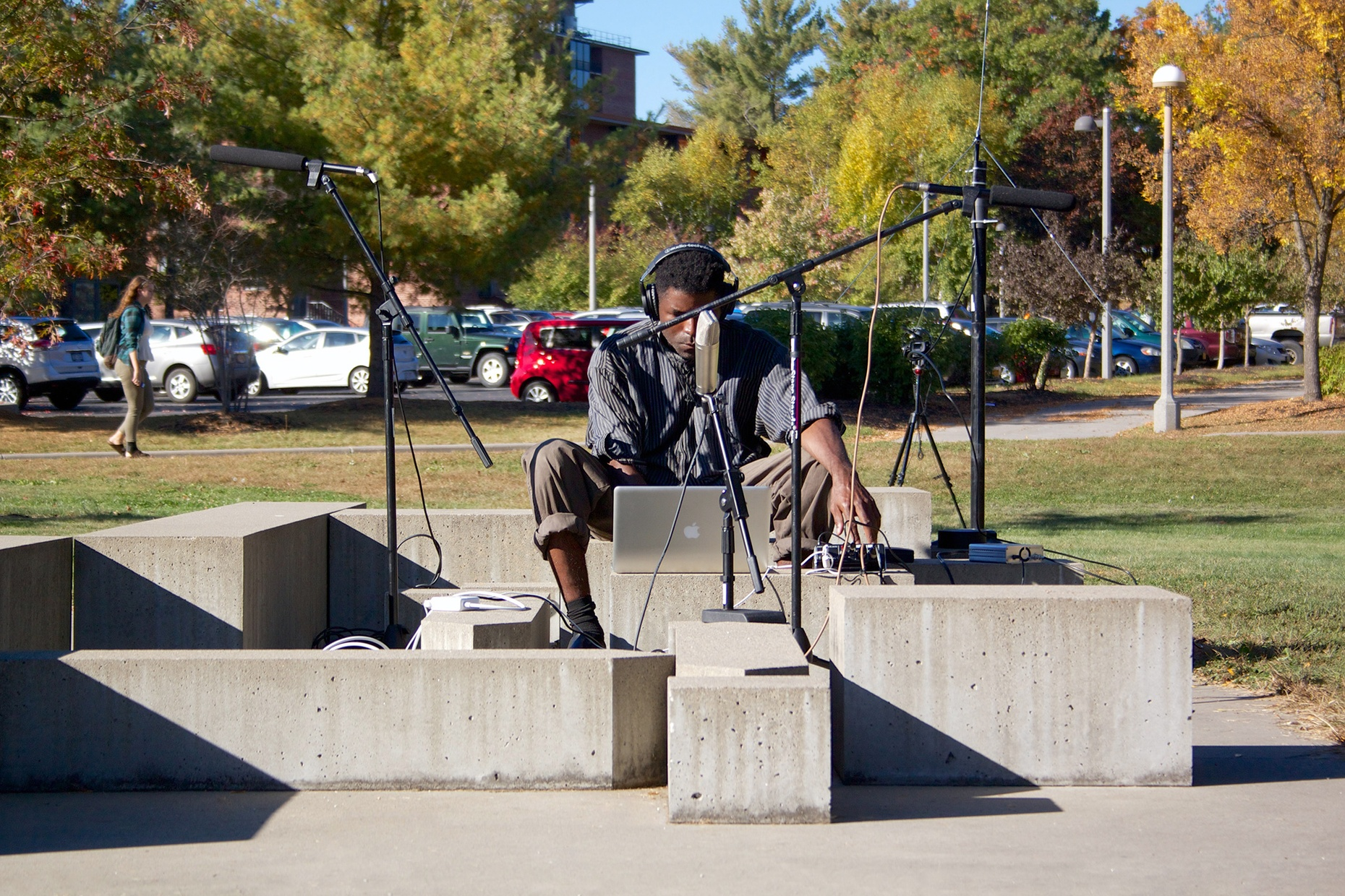 A black man sits on an outdoor sculpture made of concrete blocks with a laptop and two mics on stands.