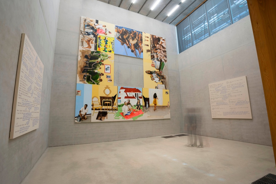 Museum installation featuring a large-scale, 11-panel work, configured as a square with a hole in the middle, featuring various, brightly painted scenes of people. Single artworks with cream-colored backgrounds and text are hung on the walls to the left and right.