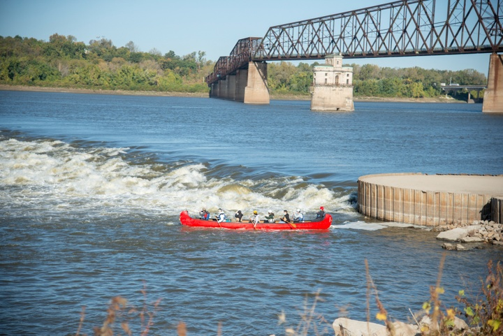 A red canoe navigates the Mississippi River downstream from the Chain of Rocks Bridge.