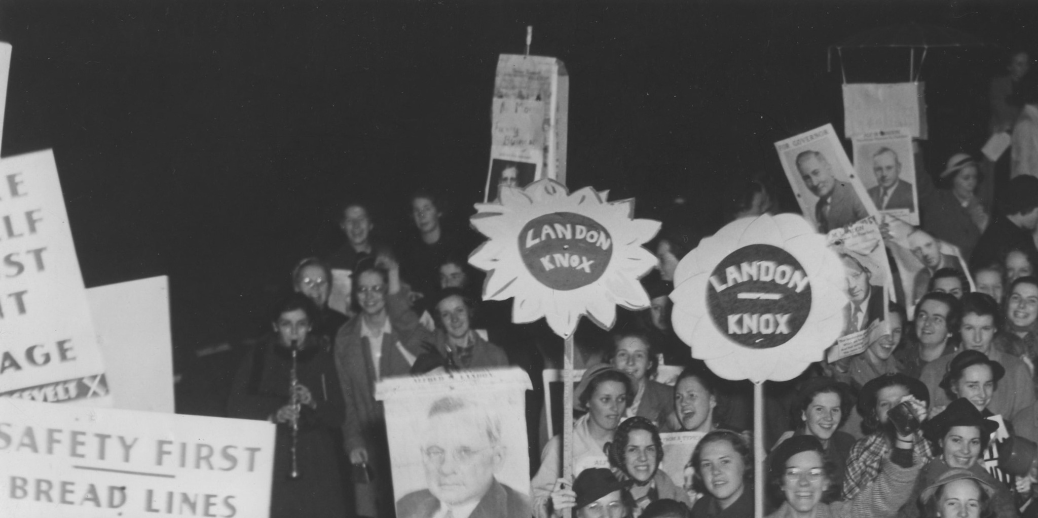 A black and white photo of a crowd of people standing holding signs in support of 1936 presidential candidates.