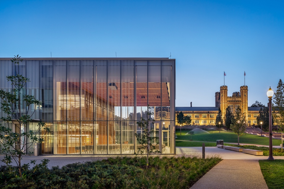 A 2-story glass-walled building seen in the foreground with the Collegiate Gothic Brookings Hall in the background, at sunset.