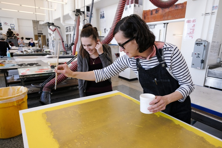 Person in black apron demonstrates dripping liquid onto a printmaking plate to another person.