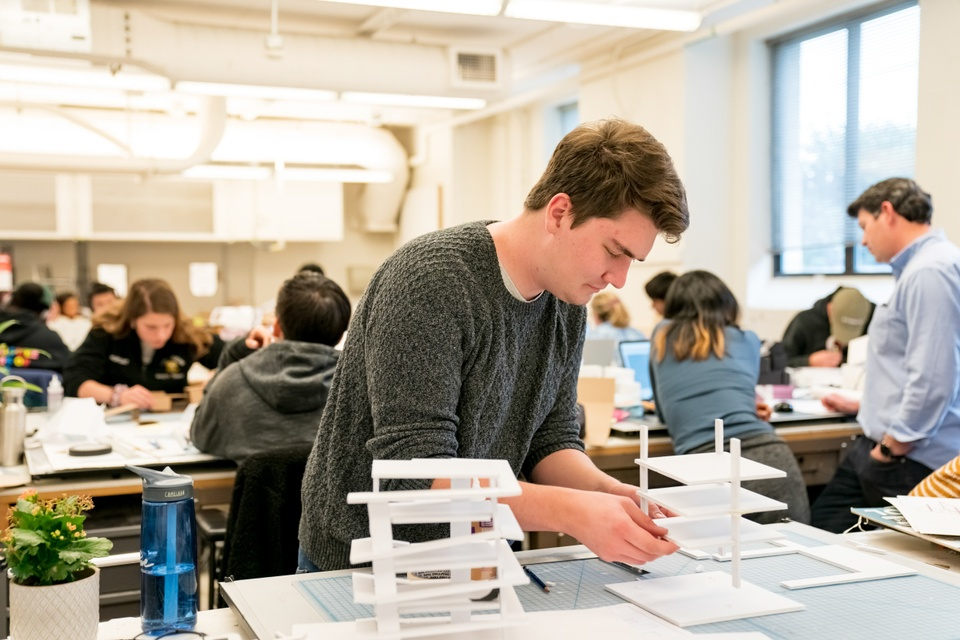 Student carefully assembles a model at a space in a large open format classroom filled with students.