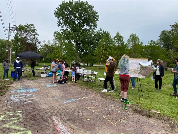 People gather around a pop-up tent with tables and displays on an empty lot with a strip of cobblestones. Children have made chalk drawings on the cobblestones. A few people inspect a posterboard with an architectural rendering on an easel.
