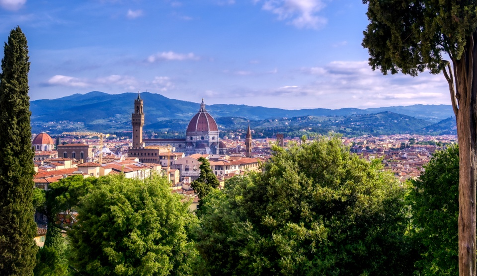Skyline view of Florence, Italy with cathedral in center and trees framing the view.