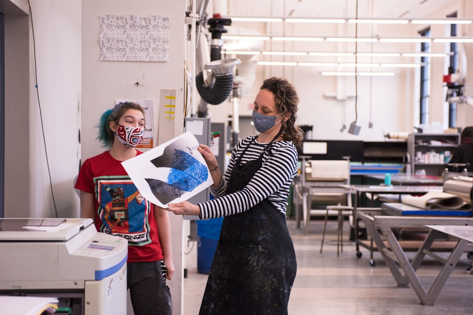 A person in a black apron stands next to a risograph machine with a person with blue hair and holds up a blue and black risograph print. Behind them is a large, well-lit space filled with printmaking presses and other equipment.