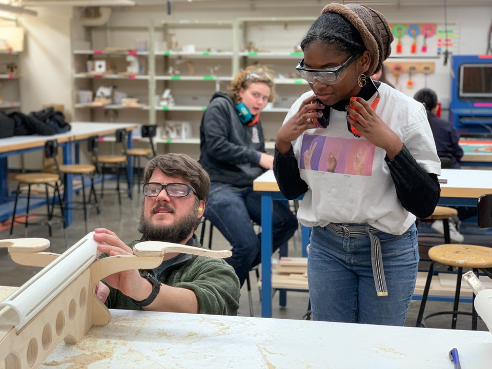 People with goggles and ear protection analyze an object made of PVC and wood in a woodshop.