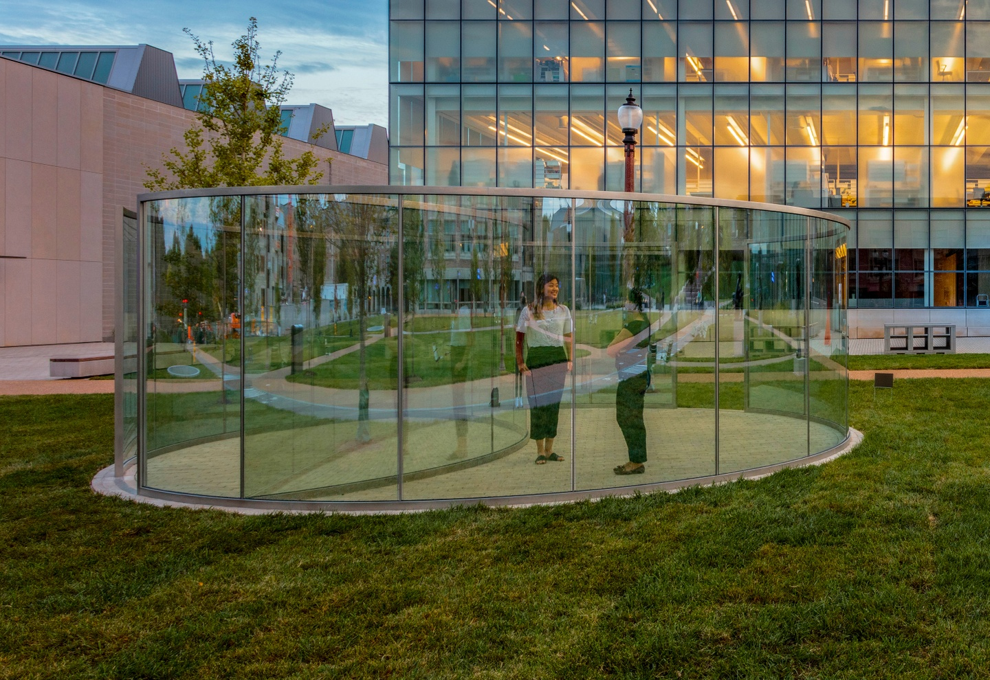 Two people stand inside a transparent pavilion