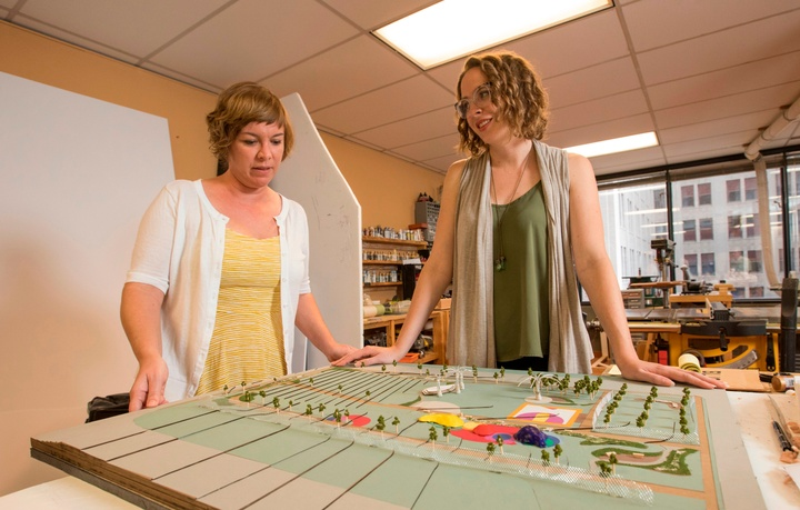 Two people stand on either side of the model of a park, looking at it.
