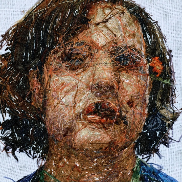 Hand embroidered portrait of a figure with dark hair that's about chin-length. The reverse side of the embroidery is shown, exposing the stitches and creating textural interest.