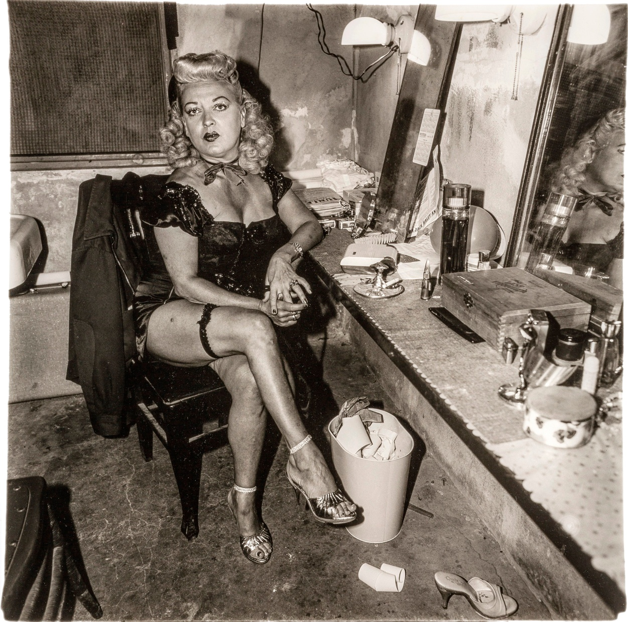A black and white photograph of a woman sitting in a chair at a dressing room mirror wearing a short, low-cut dress, garter, and high heels, with done-up hair and makeup, looking at the camera with a strait face.