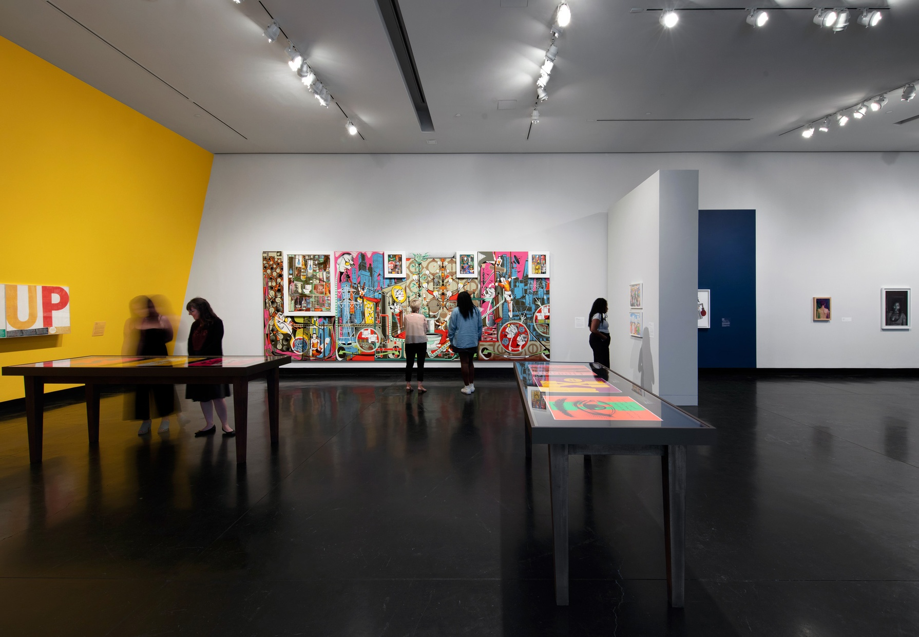 Five people look at artwork throughout a gallery space. A large, colorful abstract painting covers most of one wall.