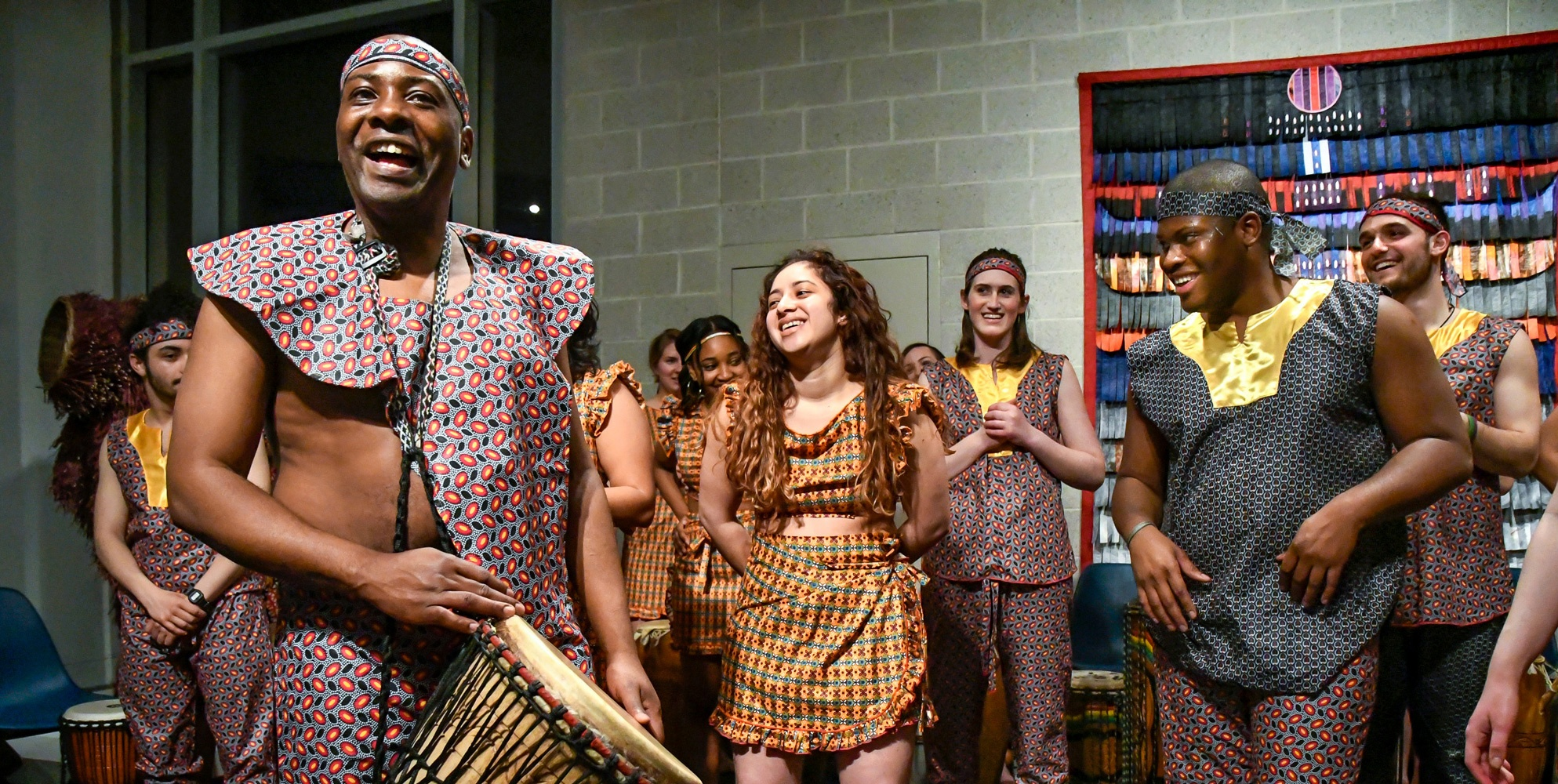 A middle-aged, black male in colorful, patterned clothing holds a bongo standing in front of a group of people wearing similar clothing.