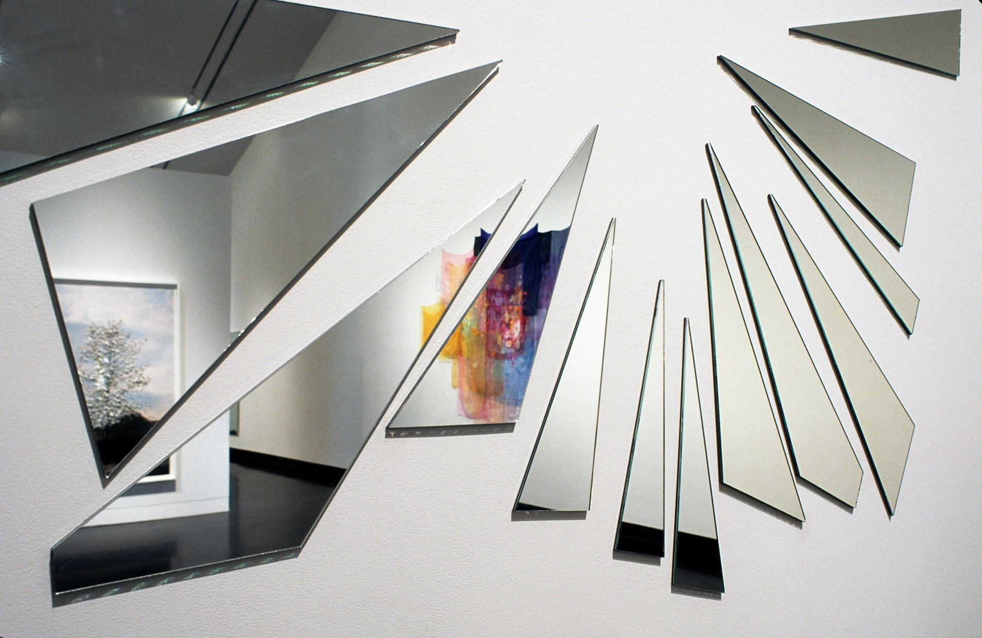 Thirteen triangular pieces of mirror hanging on a wall in a geometric pattern reflecting a gallery space.