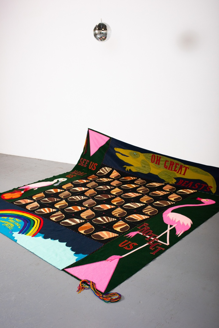 """A colorful quilt is slumped up against the white wall of a gallery space. The quilt is decorated with an alligator, a flamingo, a pelican, water, a bag of oranges, two large pink triangles, a rainbow, and a grid of spiral seashells. Letters on the quilt read """"Oh great beasts, see us, heal us, protect us."""" A miniature disco ball hangs above it."""