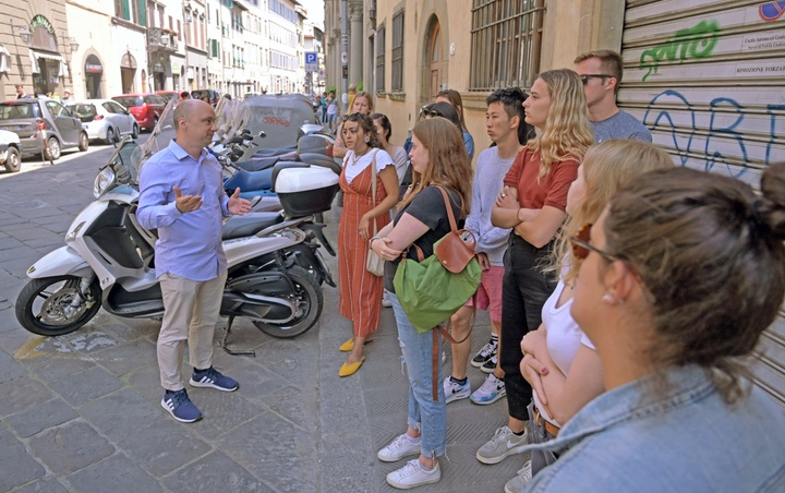 Students stand on a cobblestone street in Florence and listen to an instructor talking and gesturing.